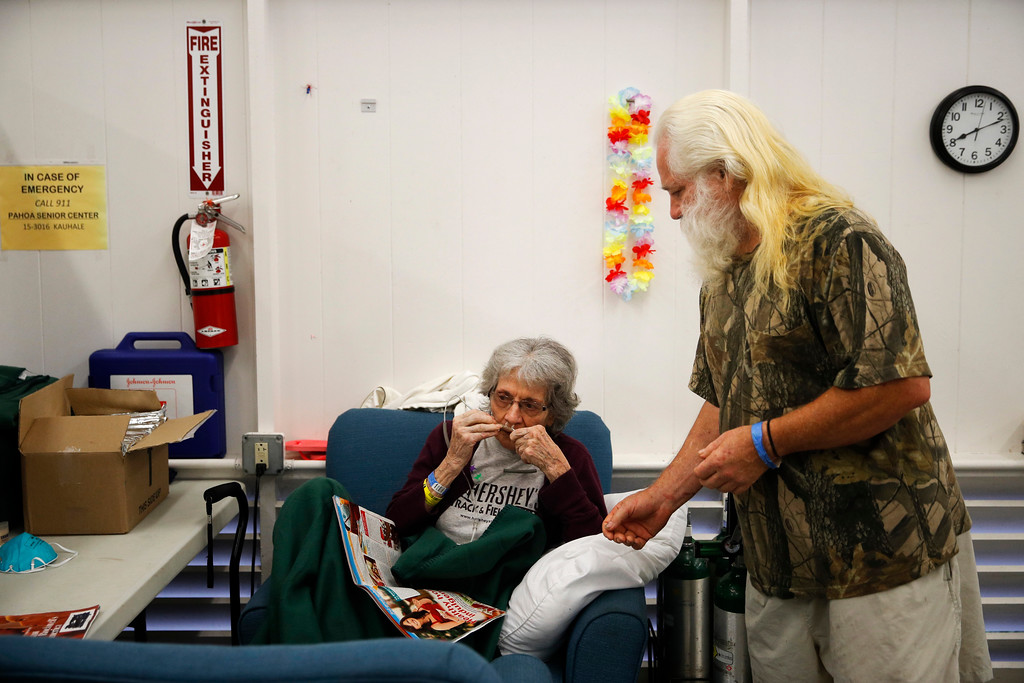. In this Friday, May 18, 2018, photo, evacuee Steve Clapper tells his mother, Euteva Bukowiecki, to wear an oxygen tube at a shelter in Pahoa, Hawaii. Hawaii residents forced to evacuate their homes because of lava oozing from cracks in their neighborhoods are growing weary. Clapper and his mother have been staying at a shelter, and he wants to get her off the Big Island because it\'s not clear when the lava threat will end. (AP Photo/Jae C. Hong)