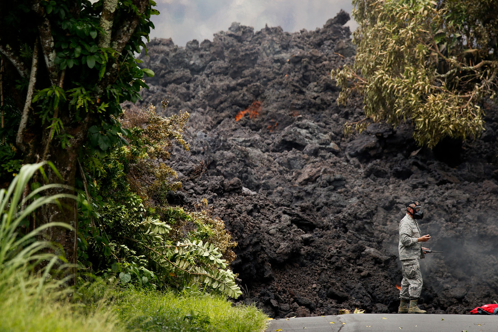 . U.S. Air Force Lt. Col. Chuck Anthony wears a gas mask as he stands next to a wall of lava entering the ocean near Pahoa, Hawaii, Sunday, May 20, 2018. Kilauea volcano, oozing, spewing and exploding on Hawaii\'s Big Island, has gotten more hazardous in recent days, with rivers of molten rock pouring into the ocean and flying lava causing the first major injury. (AP Photo/Jae C. Hong)