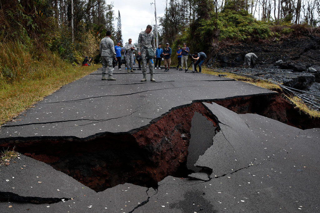 . U.S. Air National Guardsman John Linzmeier, top center, looks at cracks on the road in the Leilani Estates subdivision near Pahoa, Hawaii Friday, May 18, 2018. Hawaii residents covered their faces with masks after a volcano menacing the Big Island for weeks exploded, sending a mixture of pulverized rock, glass and crystal into the air in its strongest eruption of sandlike ash in days. (AP Photo/Jae C. Hong)