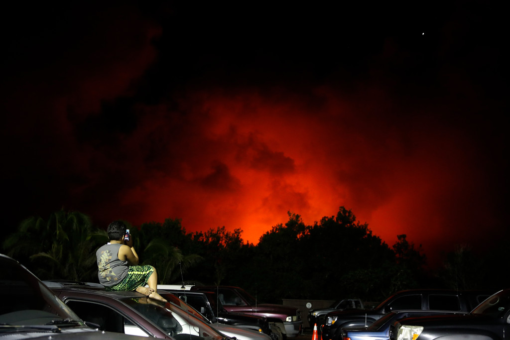 . A young boy photographs the sky turned red from lava flows in the Leilani Estates subdivision near Pahoa, Hawaii Friday, May 18, 2018. Hawaii residents covered their faces with masks after a volcano menacing the Big Island for weeks exploded, sending a mixture of pulverized rock, glass and crystal into the air in its strongest eruption of sandlike ash in days. (AP Photo/Jae C. Hong)