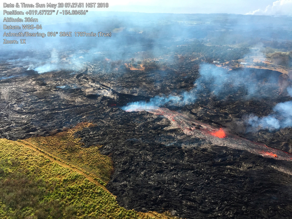 . In this Sunday, May 20, 2018, aerial photo provided by the U.S. Geological Survey, lava from the eastern channel of the Fissure 20 complex flows into a crack in the ground in Pahoa, Hawaii. Kilauea volcano began erupting more than two weeks ago and has burned dozens of homes, forced people to flee and shot up plumes of steam from its summit that led officials to distribute face masks to protect against ash particles. (U.S. Geological Survey via AP)