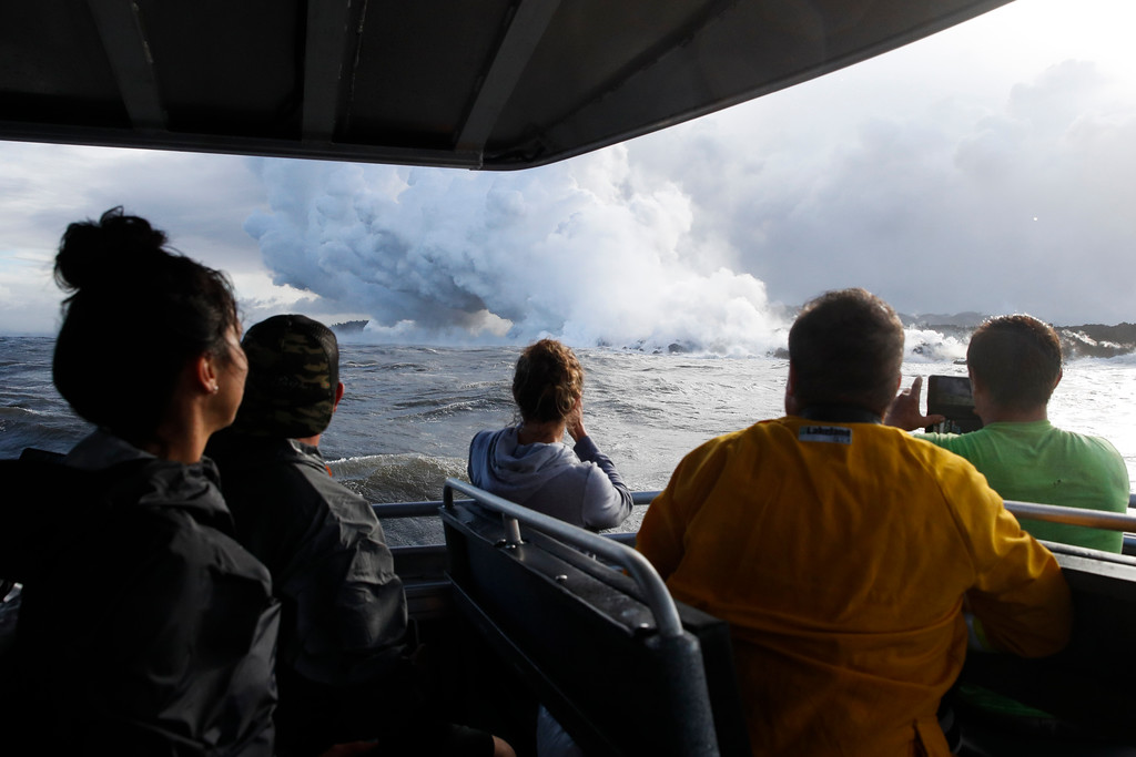 . People watch a plume of steam as lava enters the ocean near Pahoa, Hawaii, Sunday, May 20, 2018. Kilauea volcano that is oozing, spewing and exploding on Hawaii\'s Big Island has gotten more hazardous in recent days, with rivers of molten rock pouring into the ocean Sunday and flying lava causing the first major injury. (AP Photo/Jae C. Hong)