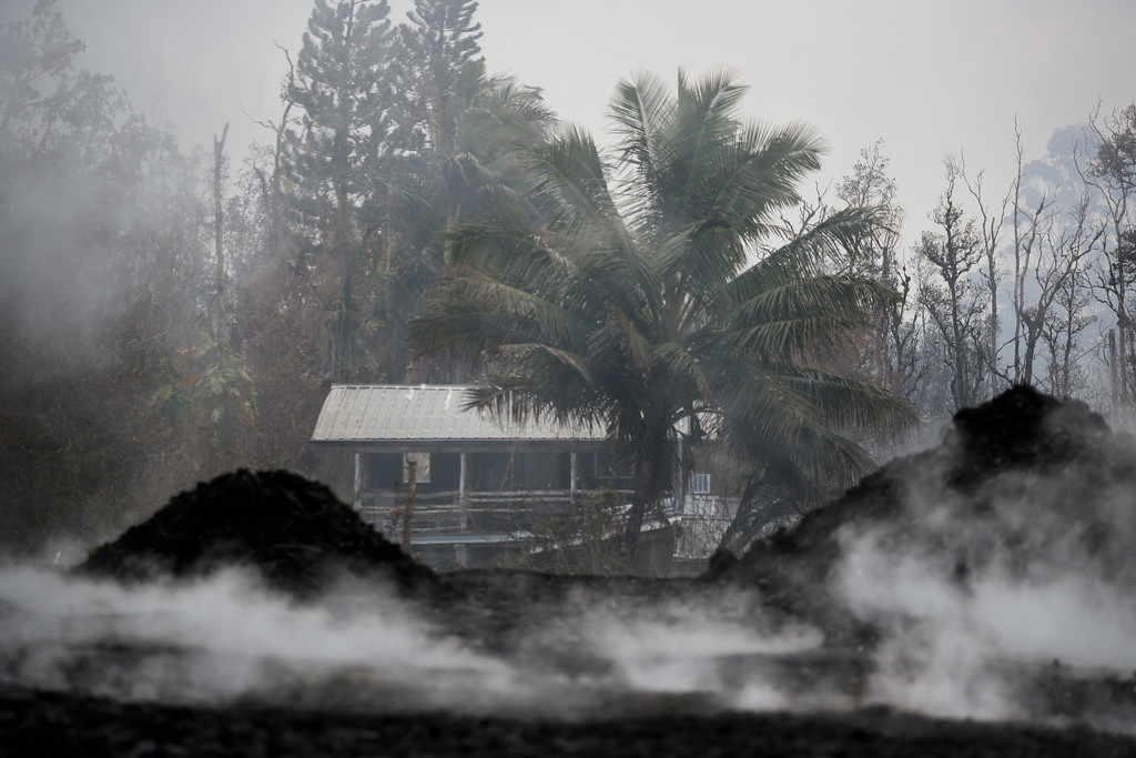 . Toxic gases rise near an abandoned home in the Leilani Estates subdivision near Pahoa, Hawaii Friday, May 18, 2018. Hawaii residents covered their faces with masks after a volcano menacing the Big Island for weeks exploded, sending a mixture of pulverized rock, glass and crystal into the air in its strongest eruption of sandlike ash in days. (AP Photo/Jae C. Hong)