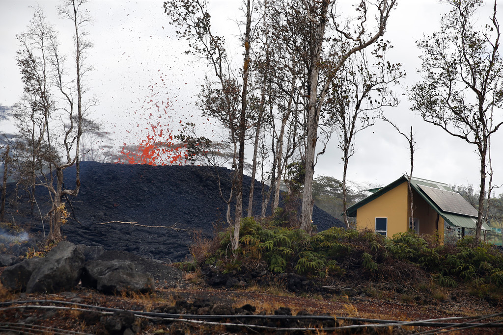 . A structure is seen next to a erupting lava fissure on Pohoiki Rd, Friday, May 18, 2018, near Pahoa, Hawaii. Hawaii residents covered their faces with masks after a volcano menacing the Big Island for weeks exploded, sending a mixture of pulverized rock, glass and crystal into the air in its strongest eruption of sandlike ash in days. (AP Photo/Marco Garcia)