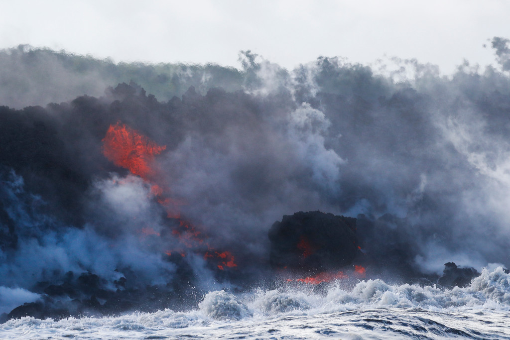 . Lava flows into the ocean near Pahoa, Hawaii, Sunday, May 20, 2018. Kilauea volcano that is oozing, spewing and exploding on Hawaii\'s Big Island has gotten more hazardous in recent days, with rivers of molten rock pouring into the ocean Sunday and flying lava causing the first major injury. (AP Photo/Jae C. Hong)
