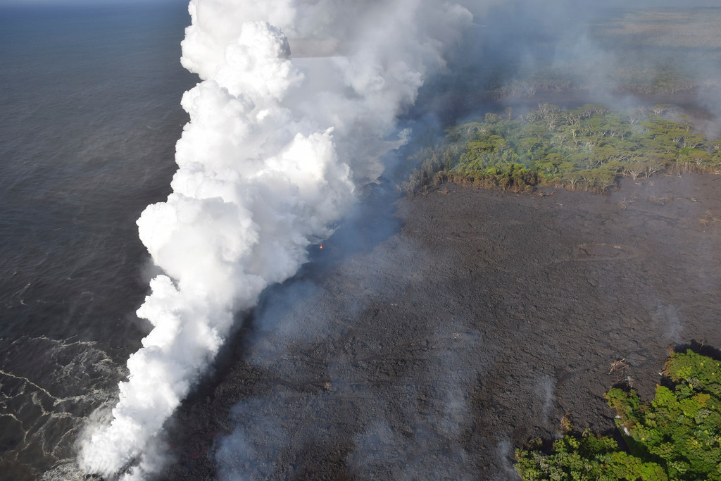 . In this image provided by the U.S. Geological Survey, lava from fissure 20 enters the ocean near Pahoa, Hawaii on Sunday, May 20, 2018. The volcano that is oozing, spewing and exploding on Hawaii\'s Big Island has gotten more hazardous, sending rivers of molten rock pouring into the ocean Sunday and launching lava skyward that caused the first major injury. (U.S. Geological Survey via AP)