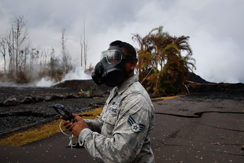 . Wearing a gas mask, U.S. Air National Guardsman Orlando Corpuz uses an SO2 detector to monitor the air quality in the Leilani Estates subdivision near Pahoa, Hawaii Friday, May 18, 2018. Hawaii residents covered their faces with masks after a volcano menacing the Big Island for weeks exploded, sending a mixture of pulverized rock, glass and crystal into the air in its strongest eruption of sandlike ash in days. (AP Photo/Jae C. Hong)