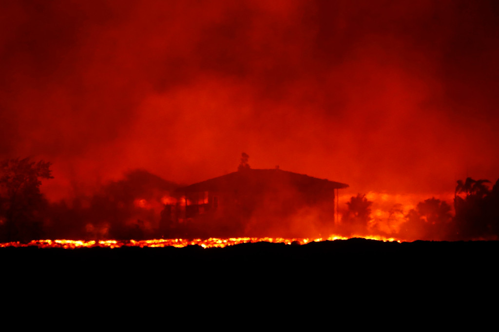 . In this May 19, 2018 photo, lava erupts near a home inside Leilani Estates near Pahoa, Hawaii. As lava flows have grown more vigorous in recent days, there\'s concern more homes may burn and more evacuations may be ordered. (Jamm Aquino/Honolulu Star-Advertiser via AP)