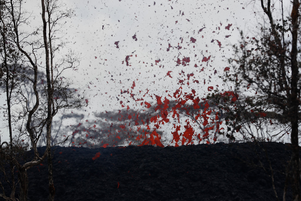 . Abe Pedro watches lava shoot out of a fissure on Pohoiki Rd, Friday, May 18, 2018, near Pahoa, HI. (AP Photo/Marco Garcia)
