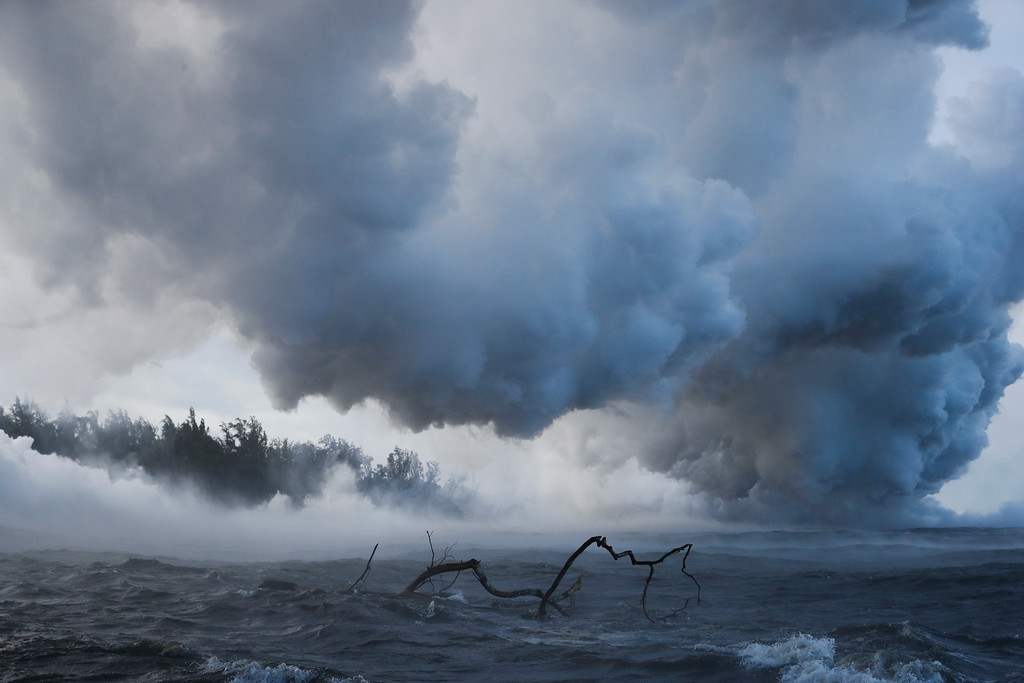 . Plumes of steam rise as lava enters the ocean near Pahoa, Hawaii Sunday, May 20, 2018. Kilauea volcano that is oozing, spewing and exploding on Hawaii\'s Big Island has gotten more hazardous in recent days, with rivers of molten rock pouring into the ocean Sunday and flying lava causing the first major injury. (AP Photo/Jae C. Hong)