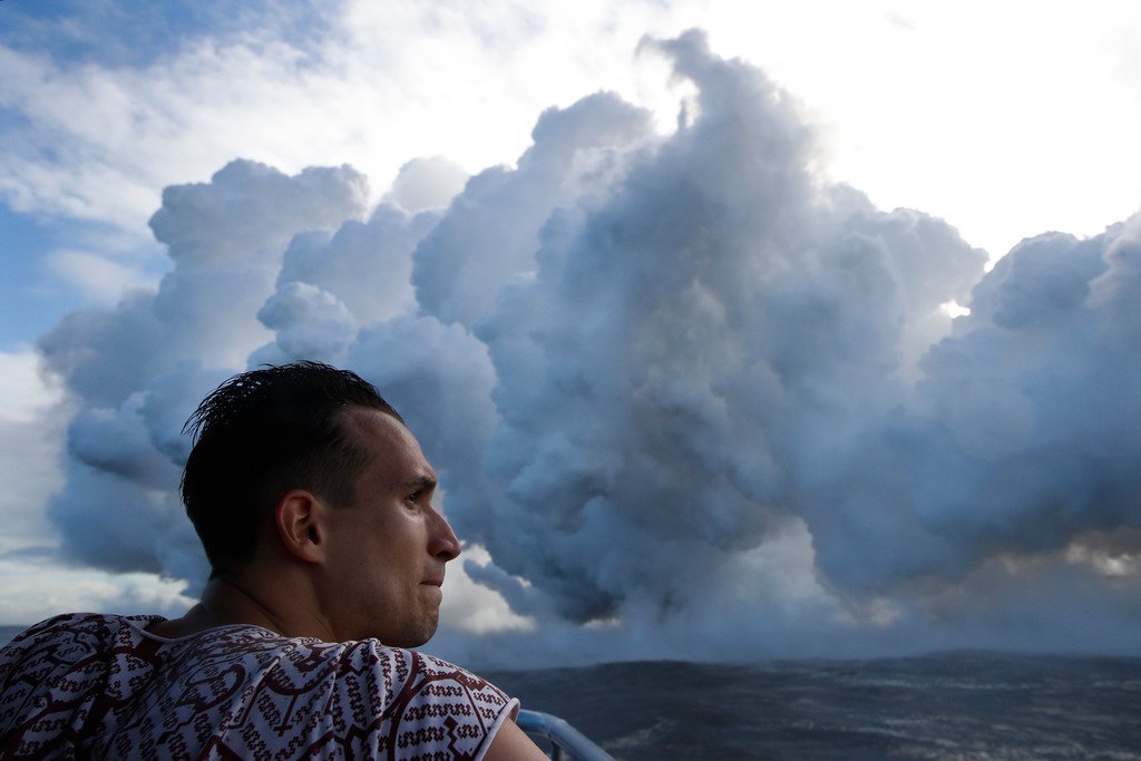 . Gabor Kovacs, visiting from Hungary, watches as lava flows into the ocean, generating plumes of steam, near Pahoa, Hawaii, Sunday, May 20, 2018. Kilauea volcano that is oozing, spewing and exploding on Hawaii\'s Big Island has gotten more hazardous in recent days, with rivers of molten rock pouring into the ocean Sunday and flying lava causing the first major injury. (AP Photo/Jae C. Hong)
