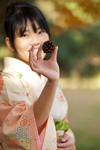 Kimono Girl with Fir Cone  Beautiful Young Japanese Woman in Kimono laughing showing Fir Cone