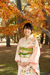 Japanese Girl in Kimono with Autumn Foliage  Beautiful Young Japanese Woman in Kimono with Autumn Foliage laughing at camera
