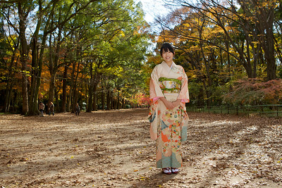 Young Japanese in Kimono, laughing at Camera  Standing in Parc with Autumn Foliage and Sunshine