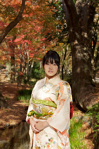 Young Japanese walking in Autumn Forest  Dressed in Kimono, looking at Camera