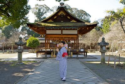 Kitano Tenmangu Shrine, Kyoto in Spring Time  Japanese Girl walking in Front of a Temple Building in Kimono