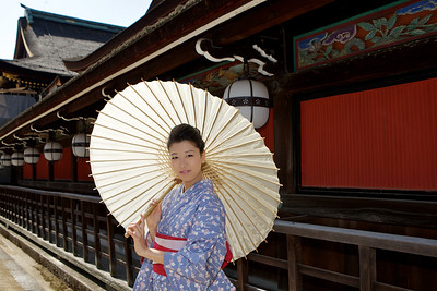 Beautiful Woman with Kimono  Posing in Front of a Temple Building