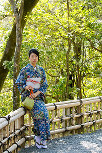 Japanese World Cultural Heritage Kinkaku-ji Temple in Kyoto  Kimono Girl sitting on a Bamboo Fence