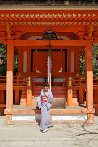 Beautiful Woman with Kimono standing in front of Shrine