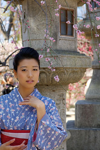 Kimono Girl Posing in Front of a Stone Lantern  With Pink Blossoms in Spring