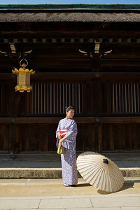 Beautiful Woman with Kimono  Posing with Parasol in Front of a Temple