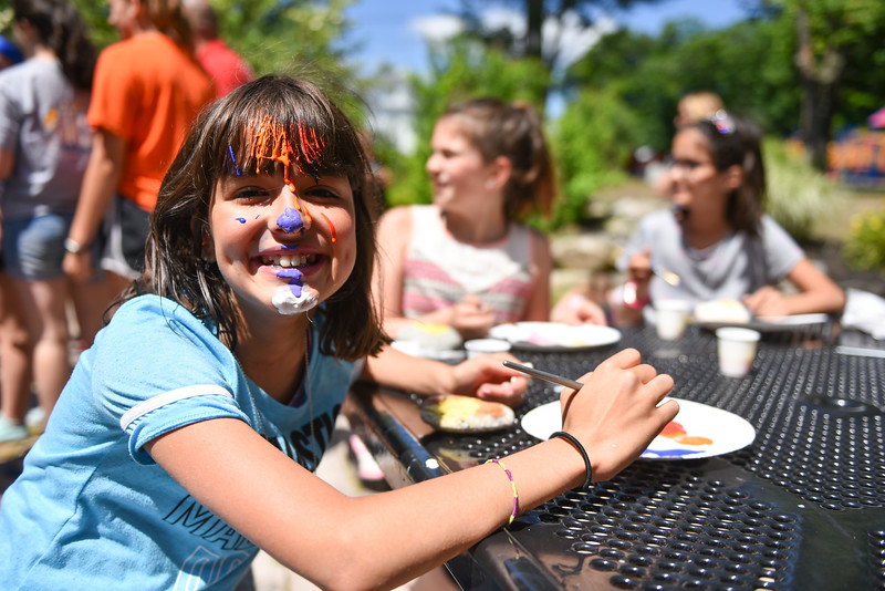 Deena Qasim, 10, of Luneburg splashes some paint on her face which we could blame on the wind, but was more the fault of the photographer, at the Lunenburg Public Library on Monday where kids and their families gather to draw inspirational messages on rocks which are to be displayed in nature throughout the community. SENTINEL & ENTERPRISE JEFF PORTER