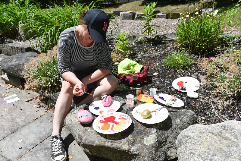 Rachel Rask of Lunenburg joins in on painting inspirational messages on rock at the Lunenburg Public Library on Monday.  SENTINEL & ENTERPRISE JEFF PORTER