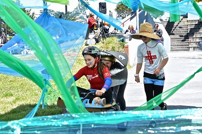 """Rogue Russell, 11, is pushed by Maile Russell, 9 and pit crewed by Sadie Breen, 11, navigate the """"water"""" crossing segment of their race.  (Jose Quezada - For the Times-Standard)"""