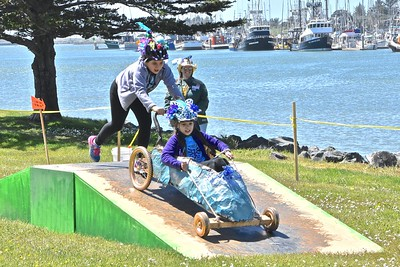 The Blue Goo Pointe Shoe goes over the incline segment of the race with Humboldt Bay in the background as Nyrie Broderick, 10, pushes Amira Wanden, 10.  (Jose Quezada - For the Times-Standard)