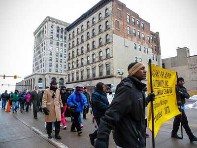 In spite of the harsh cold temperatures, a group of determined Saginawians passes through the Genesee and Washington intersection as the Unity March continues through downtown.