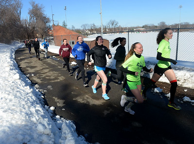 Tania Barricklo-Daily Freeman                      The Kingston High School varsity track team makes its way around the outer perimeter of Dietz Stadium during practice Friday afternoon. The path has been plowed, unlike the track below.