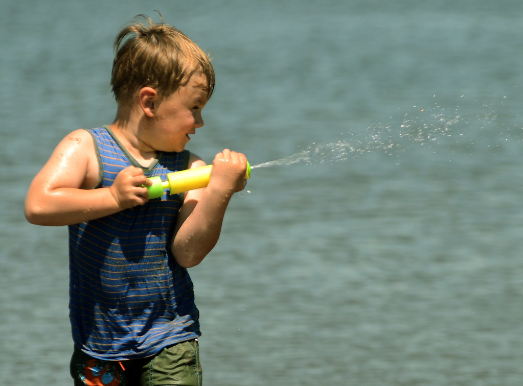 . Tania Barricklo-Daily Freeman                      Shawn Curtis, 4, son of Krystle and Jason Curtis of Lake Katrine, squirts water at his friends while cooling off at Kingston Point Beach  Wednesday afternoon.