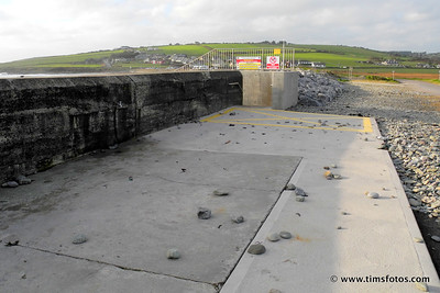 Rocks and stones thrown over the seawall by the high tide at Garretstown Beach