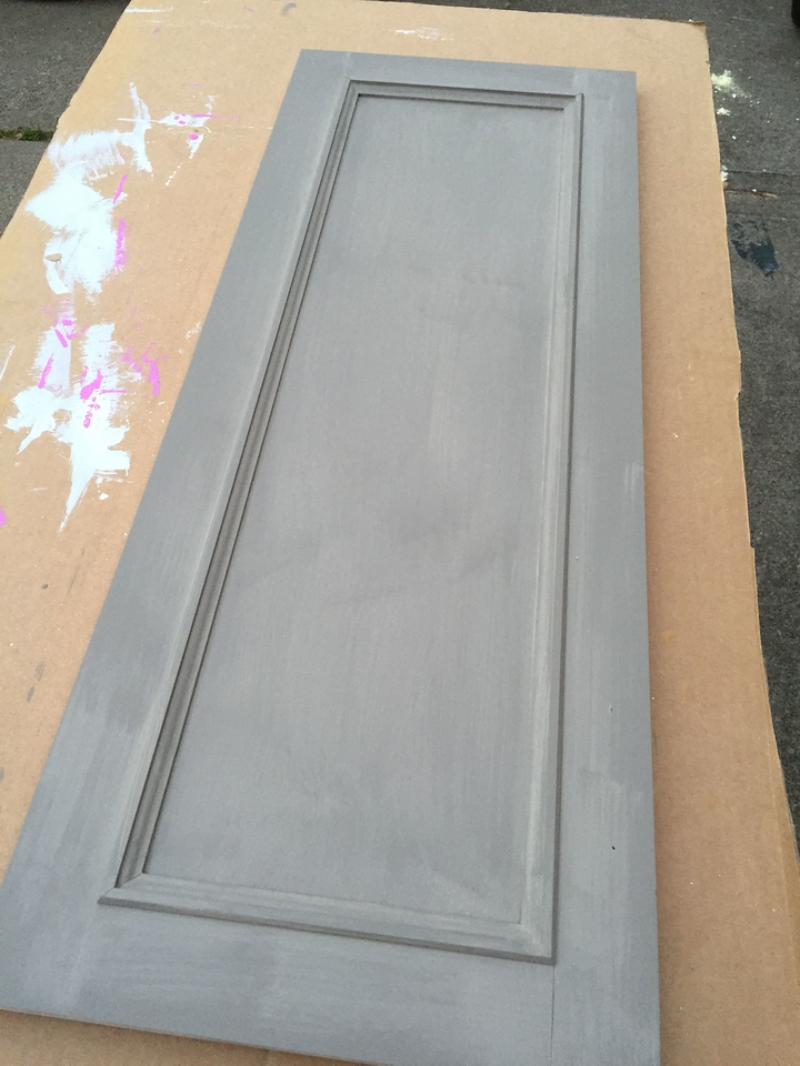 Primer on one of the doors for a wall cabinet.