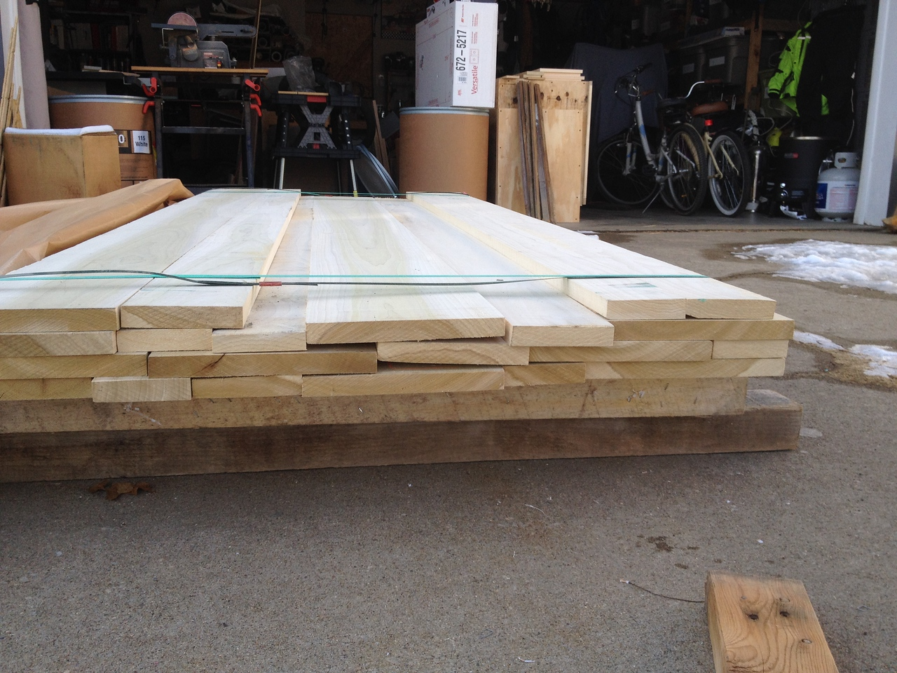 "4/4 ""Four Quarter"" poplar boards of various widths.<br /> <br /> Garage full of junk in the background."