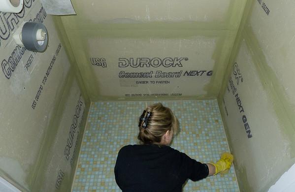 Barbara Carlson working on shower tile