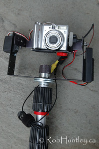 Pole Aerial Photography. This is my rig for pole aerial photography. Set up with tilt servo platform (brooxes.com) and dunecam (dunehaven.com) aerial controller (behind camera). Using CHDK and video downlink. Camera platform can be swivelled 90 degrees for verticals. It is secured with a wing nut at the back. 3/4 inch hole drilled through the centre of the brooxes main frame to permit the threads of the the paint pole to pass through. No-one sells a nut with threads to go on a paint pole, so I cut the bottom inch off an old paint roller to use as a securing nut. Two large washers were needed to take up the slack so the rig doesn't wobble. © Rob Huntley