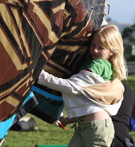 Girl helping her dad pack up the kites