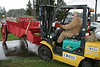 Pete Britton of the Olympic Peninsula Antique Tractor & Engine Association uses the forklift to move the red farm wagon after the front axle gave way.
