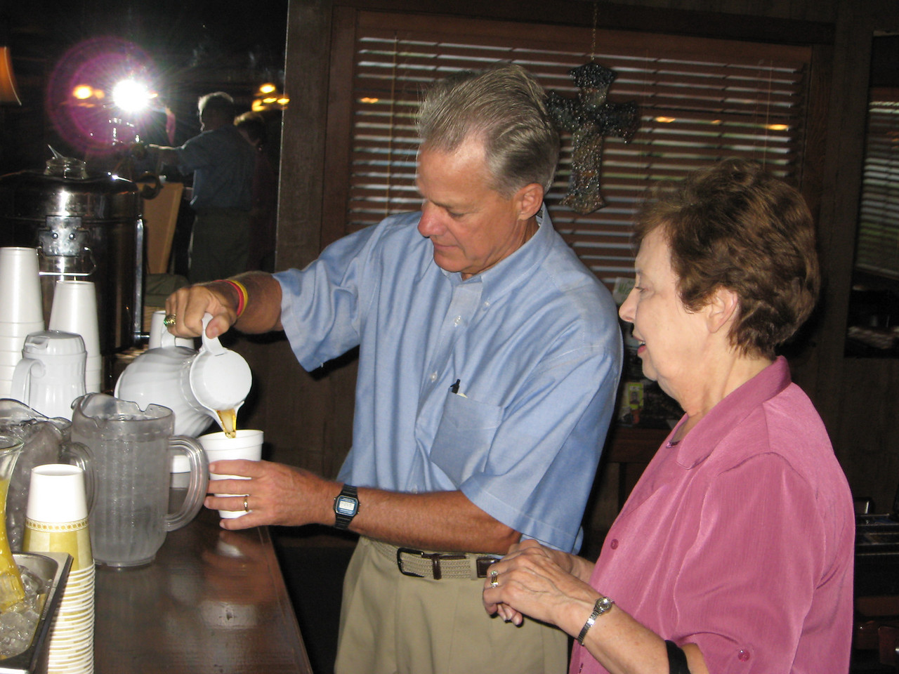 George Wilson pouring coffee for John Burch's wife and guest, Betty.