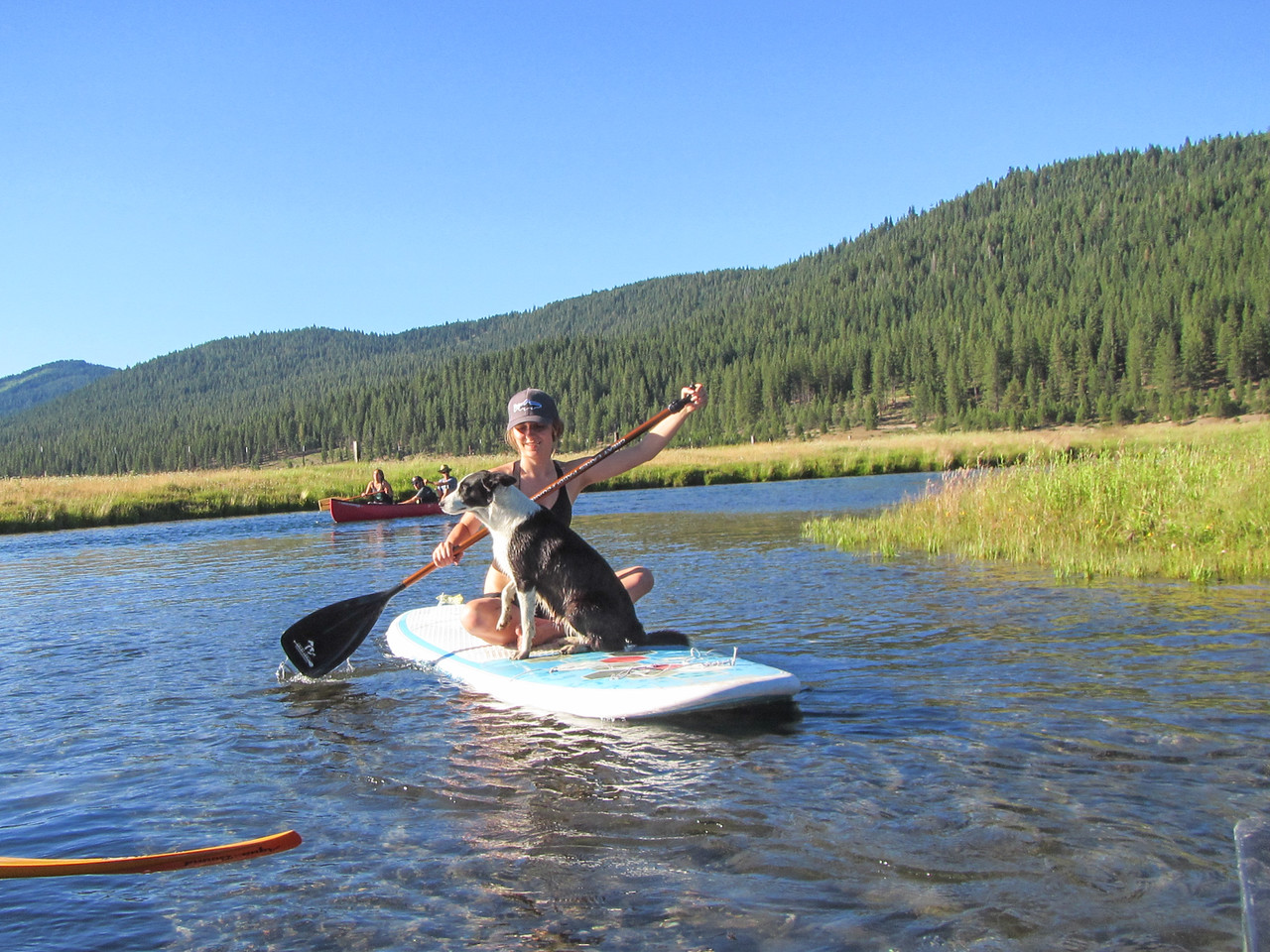 Ella Galindo paddleboards on the Wood River with a local border collie, Pipin.(Ben Lehman - Contributed photo)