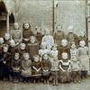 F3443<br /> Een schoolfoto uit 1898. Tussen de kinderen moet  A. van Nobelen staan. De foto is genomen bij de St. Annaschool, waar nu de Vomar is. Links de veranda, met daarachter de deur naar het 'kippenpoortje'.