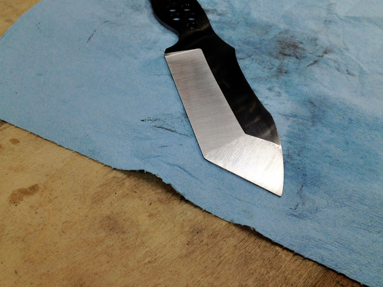 So I got a second wind and headed back out to the shop to regrind the tip of this morning's knife.<br /> <br /> It was a bit of a roller coaster.  At one point I had mucked up the tip, the main bevel, AND the flats.<br /> <br /> At that point I had nothing to lose, so I put a 60-grit on the KMG and went to work.  I was able to get the flats and main bevel repaired.  When it was time to grind the tip, I turned the KMG down to 20% and started with a 120-grit.  <br /> <br /> At one critical point I actually switched from the grinder to sandpaper.  I clamped the blade in the vice, wrapped some 220-grit paper around a G10 scale, and proceeded to finish cutting in the tip with good ole' elbow grease.  Success!<br /> <br /> I then switched back to the grinder and cleaned everything up with my typical Trizact progression.  <br /> <br /> I must say, I'm quite happy with how this knife is turning out.  I think I'm going to use black & grey G10 scales and my dark stonewashed finish on this one.