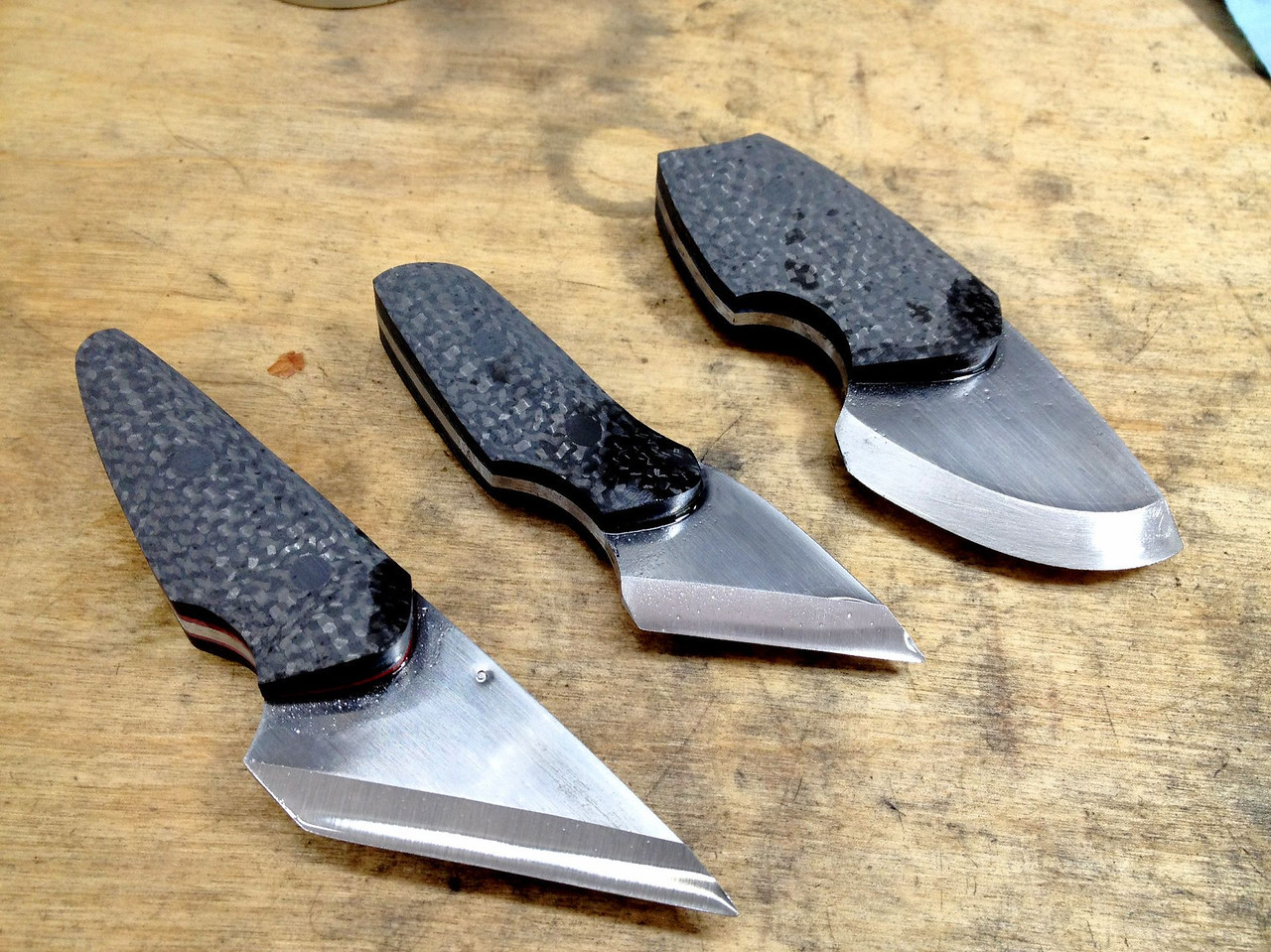"""It was now time to shape the scales.  I started with a slack 120-grit and slowly removed material until things started to feel right.  It quickly became apparent that a finger relief near the front of the scales would improve the ergonomics.<br /> <br /> For the two straight-edged knives, I used the 1"""" small wheel to grind the relief.  For the curved-edge knife, I used the 10"""" wheel to grind the relief.<br /> <br /> I then finished them on the slack belt.  Here they are before going into the tumbler."""