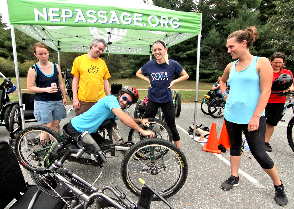 . Checking out this new type of off-road trike wheelchair is Greg Durso 33 of Stony Brook, NY, and looking on is L-R, Chelsea White, Jonathan Martel, Nicole Bartlebaugh and Anna Hausermann (both with MGH/IHP program), all at the 4th annual Knobby Tire Ride and Roll event for the Empower Spinal Cord Injury held at Great Brook Farm State Park in Carlisle. SUN/David H. Brow