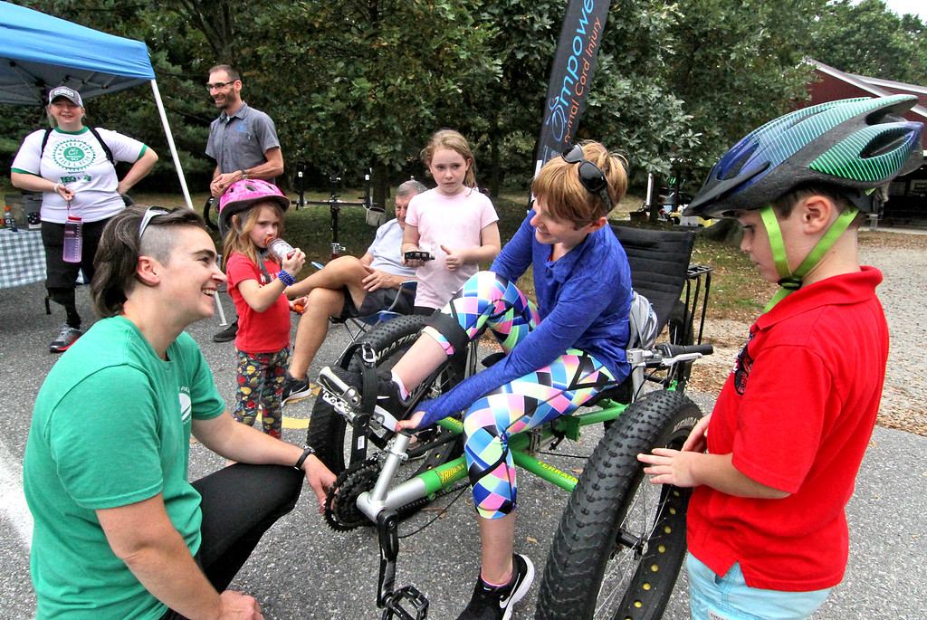. NorthEast Passage company rep Crystal Skahan of Durham NH, on left, helps Kara Spurr of Wilmington get set-up in a Fat Trike wheelchair, as Crystal\'s children look on L-R, Eisley Skahan 6, Molly Skahan 9, and Grady Skahan 7. SUN/David H. Brow