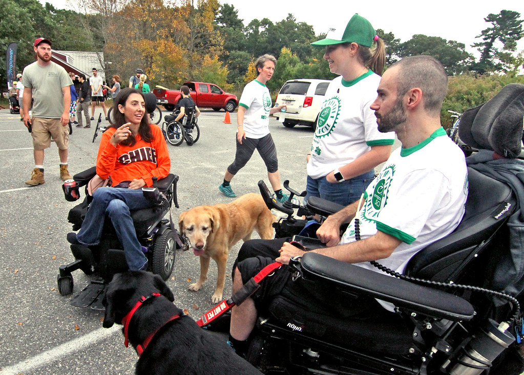 . Talking at the 4th annual Knobby Tire Ride and Roll event is L-R, Stephaine Zaia with her service dog Izzy, to the two event co-cootinators Kelly Spellman and Ryan DeRoche with his dog Oliver. SUN/David H. Brow
