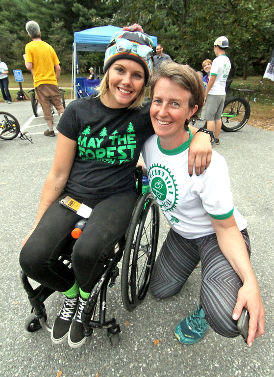 . Empower Spinal Cord Injury volunteer Brenna Bean gets a hug from Carrie Callahan President/Co-Founder of Empower Spinal Cord Injury at the 4th annual Knobby Tire Ride and Roll event at Great Brook Farm State Park in Carlisle. SUN/David H. Brow
