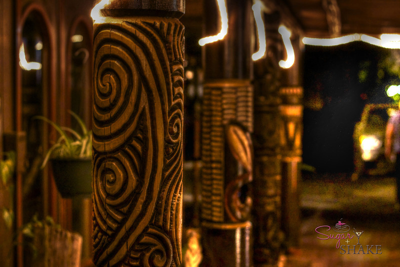 Carved old-timey tiki pillars line the walkway. (They're everywhere inside, too.) © Sugar + Shake
