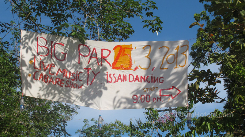 sign showing a party with isan dancers near Baan Koh Jum Village Koh Jum